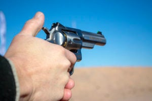 White male pointing a single-action revolver downrange against a sandy berm and a clear blue sky. His thumb is poised to manually cock the hammer spur.