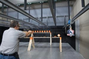White male with a receding hairline, ear protection, gray polo shirt and black OWB holster fires a black semi-automatic pistol at a line of orange disk targets at an indoor range