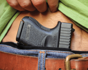 A compact Glock pistol tucked into an AIWB holster at the front of a man's jeans. A hand is lifting a neon green shirt to expose the grips of the gun as well as the man's hairy navel.