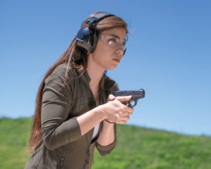 """A young brunette woman with long hair and a long-sleeved olive drab shirt holds a black concealed carry pistol close to her sternum in a position called """"high compressed ready."""" The shooter is wearing eye and ear protection at an outdoor gun range."""