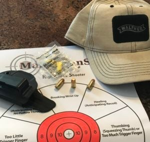 A tan baseball cap with a black Walther patch on the front, a black inside-the-waistband (IWB) holster, a clear bag contaning a pair of bright yellow foam earplugs and three rounds of .380 wadcutter pistol ammunition lie atop a right-hand shooter aim correction paper target with a red bullseye.
