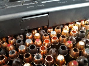 View of the flat top of a 10mm Glock 20 semi-automatic pistol. The gun is lying on its side atop a variety of 10mm peronal defense ammunition sporting variations in composition and utility.