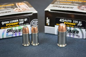 Three SIG-Sauer VCrown JHP cartridges featuring nickel-plated casings and brass-jacketed bullets. Two are 9mm and one is .45 ACP. The rounds stand in front of their respective retail boxes.