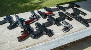 A variety of handguns of all styles and calibers, including both evolvers and semi-automatic pistols, laid out on a bench at an outdoor shooting range.