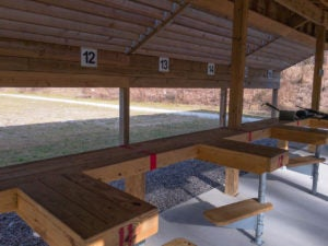 Numbered stalls and benches at an outdoor gun range.
