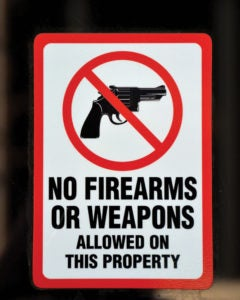 """A vertical white sign with a red border. It depicts the silhouette of a revolver inside of a red circle and slash (the international sign for """"forbidden"""") above the words NO FIREARMS OR WEAPONS ALLOWED ON THIS PROPERTY"""