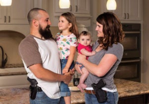 A father and mother each hold a small child in their arms while wearing holstered pistols on their belts. The setting is a residential kitchen.