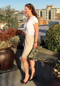 A pretty woman in a white blouse, tan skirt and high heels on an outdoor patio in the city. Her bejeweled clutch is a fashionable way to conceal a firearm.