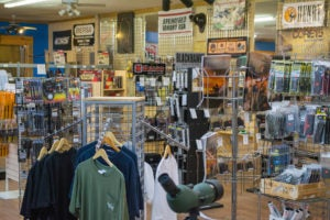 Your typical gun store room featuring display racks of optics, literature, magazines, cleaning kits and other accessories amid advertisements and displays for firearm accessory and ammunition manufacturers.