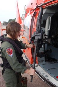 A young woman in an olive drab Coast Guard flight suit inspects the machine gun attached to the pen door of an orange Coast Guard helicopter.