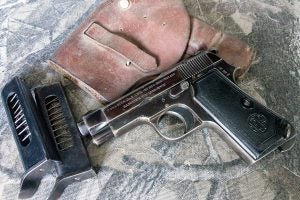 A Beretta Model 1934 lying on a camouflage background beside a weahered leather holster and a plastic magazine.