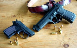 Two Beretta handguns lying on a wooden tabletop next to a reddish-brown leather belt and a handful of ammunition.